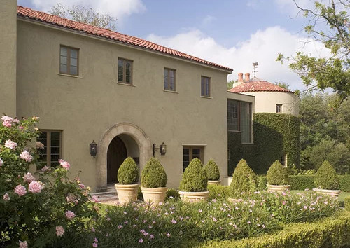 A Tuscan Flare With A Very Light Green Stucco Exterior