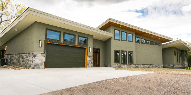 Sleek And Modern Design Showing Off The Green Stucco And Gray Rocks