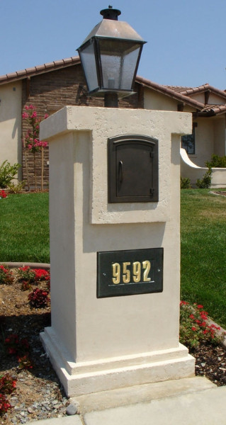 A Light Colored Stucco Mailbox With Darker Accents