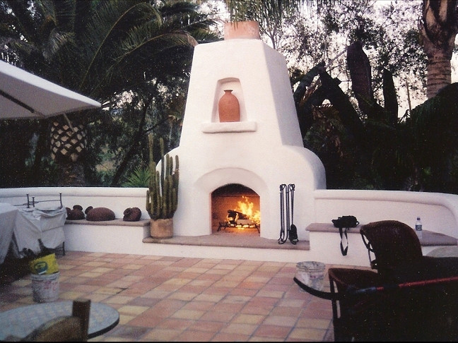 A Simple White Stucco Fireplace With A Fire