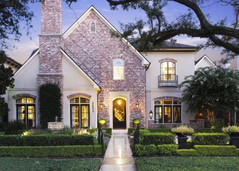 A Beautiful Home With Light Stucco And Red Brick