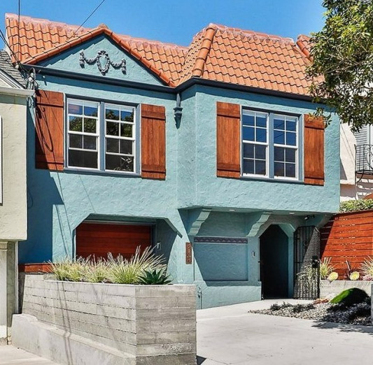 A Teal Colored Stucco House With Stained Wood Accents