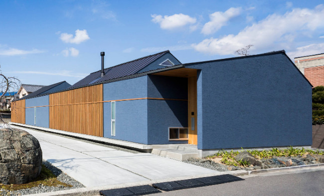 Blue Stucco With Stained Wood And Metal Roof