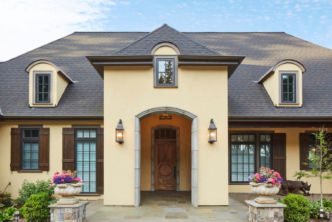 Light Yellow Stucco With Dark Roof And Shutters